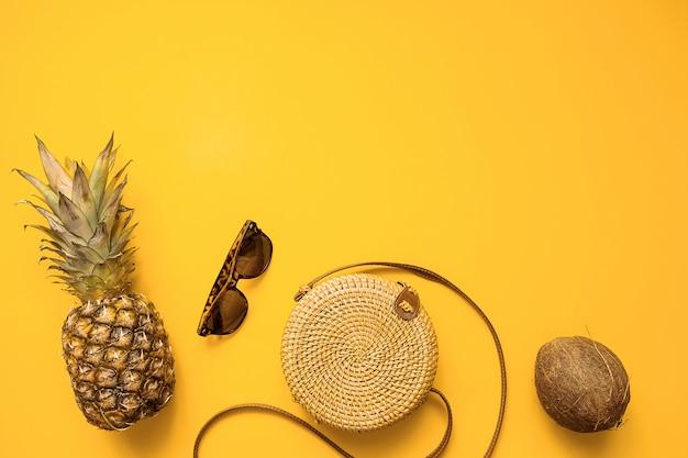 Kleurrijke zomer vrouwelijke mode outfit plat lag met bamboe tas, zonnebril, kokosnoot, ananas Premium Foto