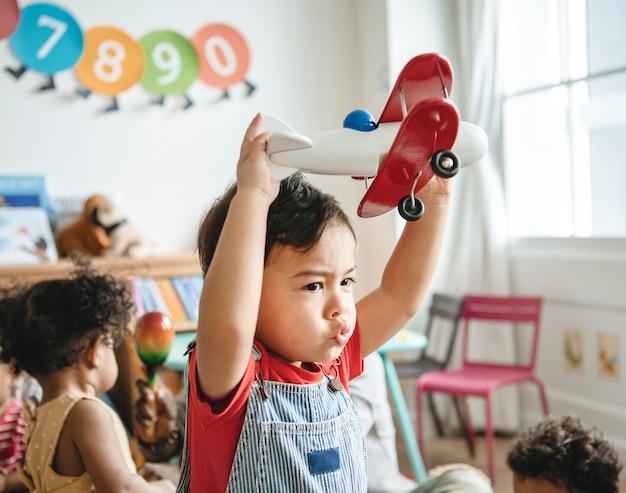 Kleuter die geniet van speel met zijn vliegtuigstuk speelgoed Premium Foto