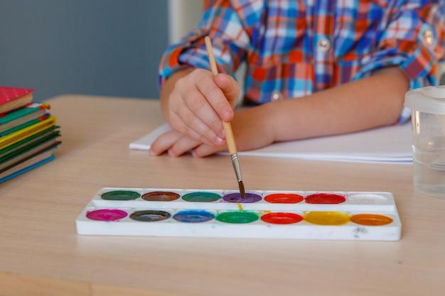 Kleuters tekenen i. baby houdt een penseel in de hand en schildert verven. het concept van de ontwikkeling van kinderen Premium Foto