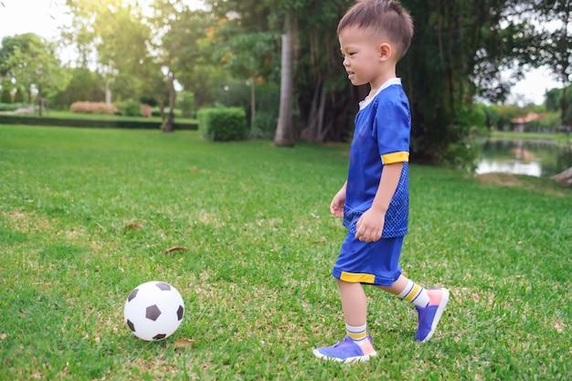 Kleuterschooljongen in voetbaluniform speelt voetbal Premium Foto