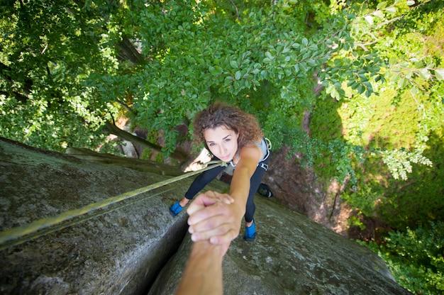 Klimmer die vrouwelijke klimmer helpen om een bovenkant van berg te bereiken Premium Foto