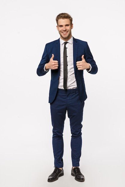 Klinkt goed, ik zit erin. verticaal schot over de volledige lengte knappe mannelijke ondernemer in klassiek elegant pak, stropdas, duimen opdagen, glimlachend goedkeuring geven, als interessant idee, witte achtergrond Premium Foto
