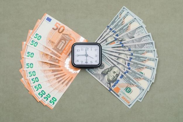 Klok, dollar en euro biljetten op groen grijze tafel. Gratis Foto