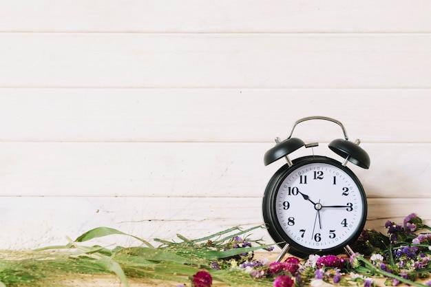 Klok en verschillende bloemen Gratis Foto