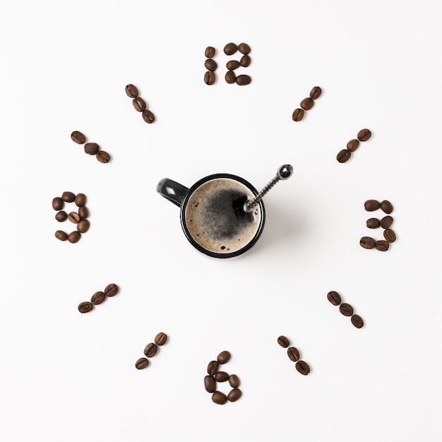 Klok gemaakt van koffiebonen en mok Gratis Foto