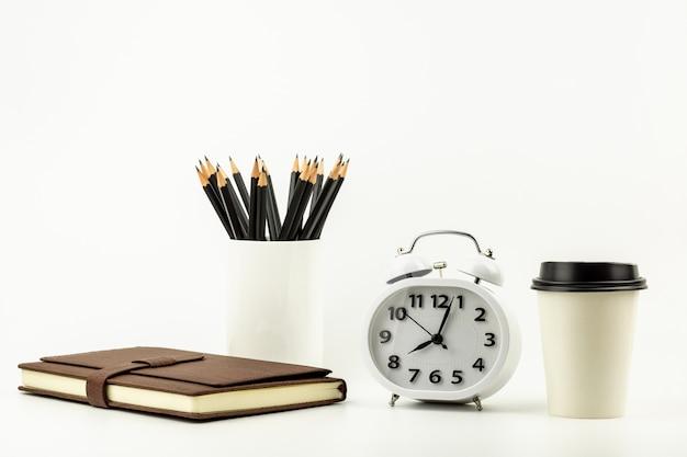 Klok, koffiekopje, potlood en een lederen laptop op witte bureau achtergrond met kopie ruimte Premium Foto