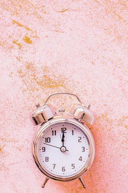 Klok met pailletten op roze tafel Gratis Foto