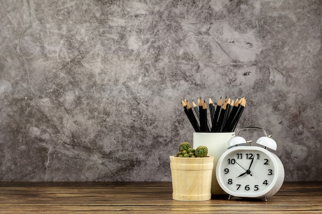 Klok, potlood en een kleine cactus op houten bureau Premium Foto