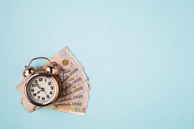 Klokwekker met thaise munt, 1000 baht, geldbankbiljet van thailand op blauwe achtergrond voor zaken, financiën en tijdbeheerconcept Premium Foto