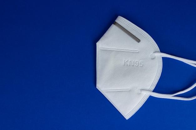Kn95 of n95 wit masker met antiviraal medisch masker voor bescherming tegen coronavirus op blauw Premium Foto