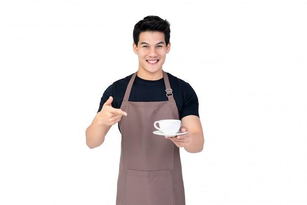 Knap het glimlachen aziatisch de studioschot van de barista dienend die koffie op witte achtergrond wordt geïsoleerd Premium Foto