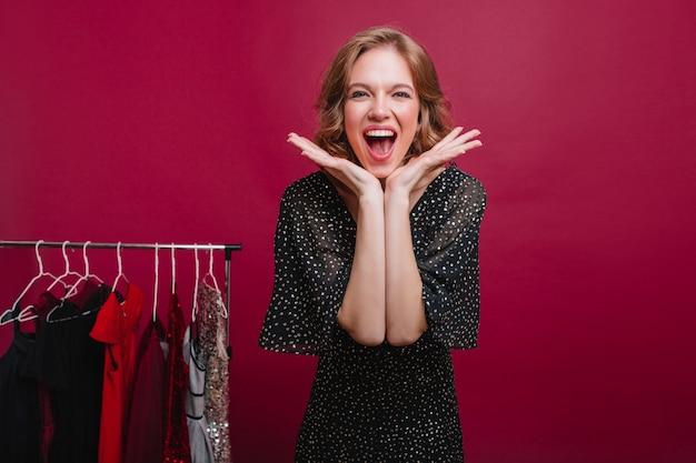 Knap lachend meisje dat op partij wacht en kleding kiest Gratis Foto