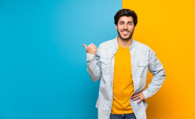 Knap over geïsoleerde kleurrijke muur die aan de kant richt om een product te presenteren Premium Foto