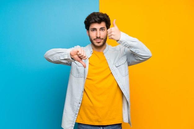 Knap over geïsoleerde kleurrijke muur die goed-slecht teken maakt, onbeslist tussen ja of niet Premium Foto