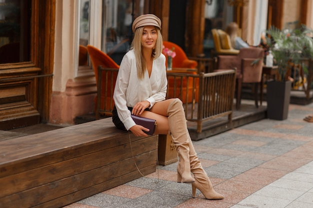 Knap sexy blond model in witte blouse en leren skrt en gebreide blokdijhoge laarzen in beige Gratis Foto