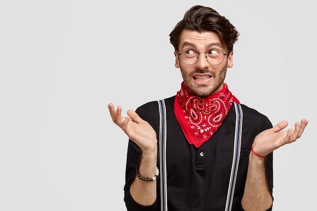Knappe aarzelende man haalt zijn schouders op, kijkt twijfelend opzij, weet niet wat hij moet zeggen, draagt een stijlvol shirt en een rode bandana om de nek Gratis Foto