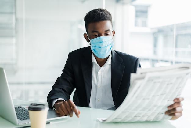 Knappe afrikaanse zakenmanslijtage in medisch masker met krant in de ochtend dichtbij commercieel centrumbureau Gratis Foto