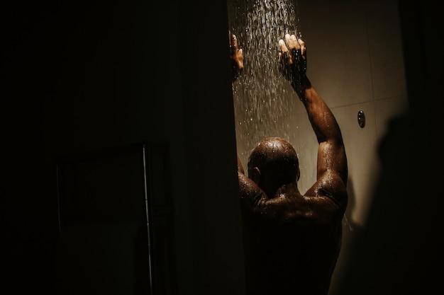 Knappe afro-amerikaanse man met naakte torso neemt douche Gratis Foto