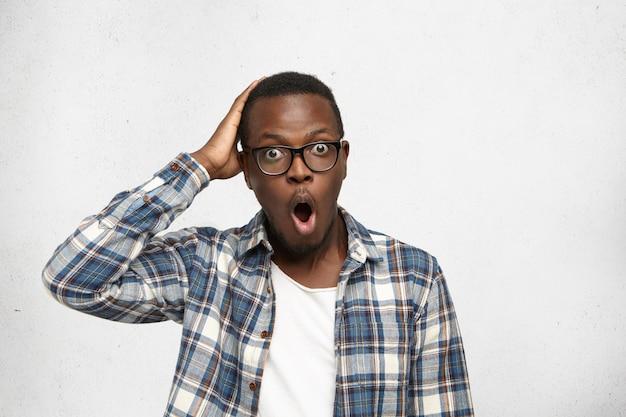 Knappe afro-amerikaanse mannelijke freelancer met bug-ogen in overhemd met vergeetachtige gezichtsuitdrukking, hoofd met hand aanrakend, realiserend dat vandaag de deadline van zijn project is, mond openend alsof hij nee zegt! Gratis Foto