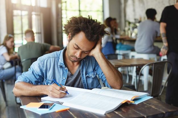 Knappe afro-amerikaanse mannelijke student die zich moe en gestrest voelt terwijl hij zijn huiswerk opnieuw moet doen, probeert zich te concentreren op de taak en te ontdekken waar hij een fout heeft gemaakt, starend naar schrift met geconcentreerde blik Gratis Foto
