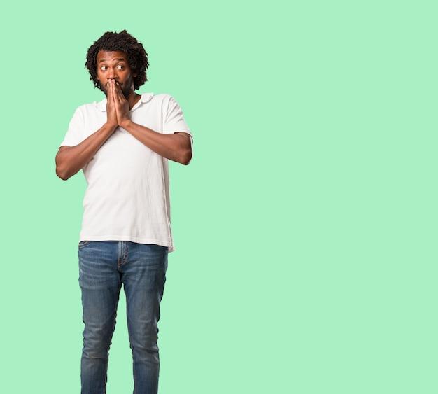 Knappe afro-amerikaanse zeer bang en bang, wanhopig op zoek naar iets, huilt van lijden en open ogen, concept van waanzin Premium Foto