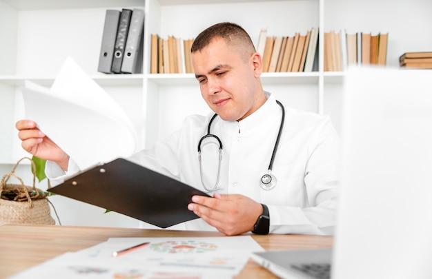 Knappe arts die een klembord houdt Gratis Foto