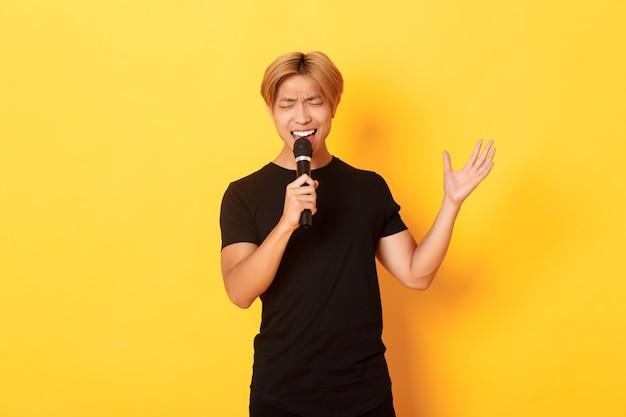 Knappe aziatische mannelijke zanger, koreaanse kerel die lied zingt bij karaoke in microfoon met hartstocht, die zich over gele muur bevindt Gratis Foto