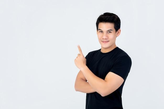 Knappe aziatische mens die en hand omhoog naar lege ruimte glimlacht richt Premium Foto