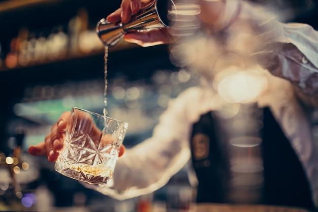 Knappe barman drinken en cocktails aan een balie maken Gratis Foto