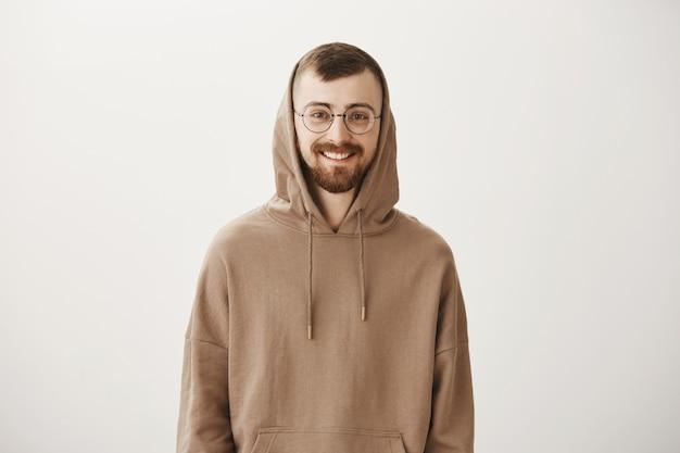 Knappe bebaarde hipster man in hoodie en glazen glimlachen Gratis Foto