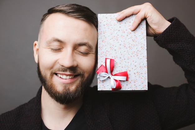 Knappe bebaarde man glimlacht en houdt de ogen gesloten terwijl hij een mooi cadeau in de buurt van het gezicht vasthoudt en op een grijze achtergrond staat Premium Foto
