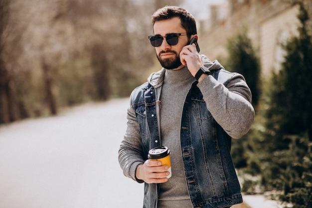 Knappe bebaarde man koffie drinken buiten de straat Gratis Foto