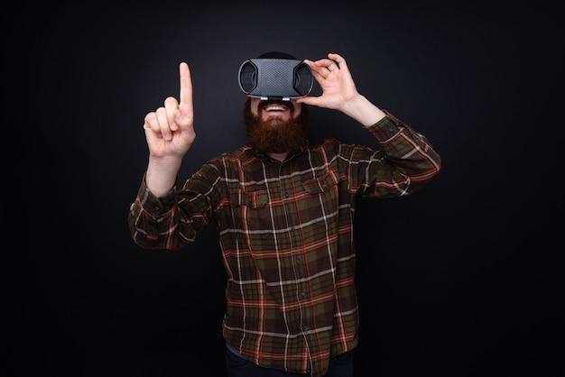 Knappe bebaarde man met behulp van vr bril en probeert iets, over donkere muur te raken Premium Foto
