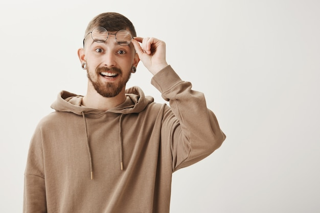 Knappe bebaarde man opstijgen bril en kijkt opgewonden, glimlachend gelukkig Gratis Foto
