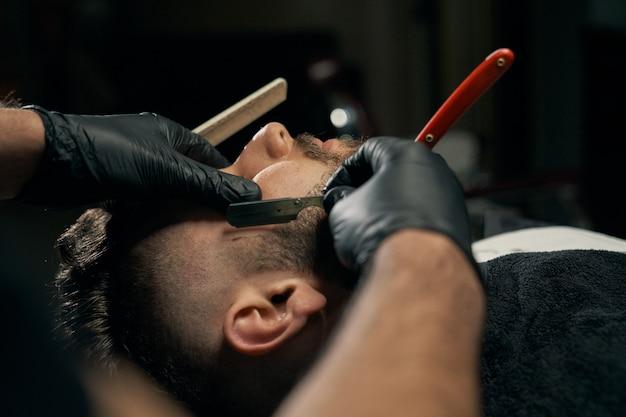 Knappe, bebaarde man wordt geschoren door kapper Premium Foto