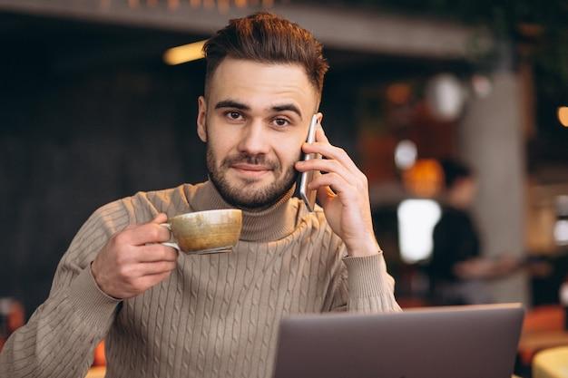 Knappe bedrijfsmens die aan computer en het drinken koffie in een koffie werkt Gratis Foto