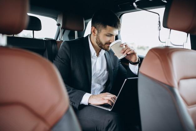 Knappe bedrijfsmens die aan een computer in auto werkt Gratis Foto