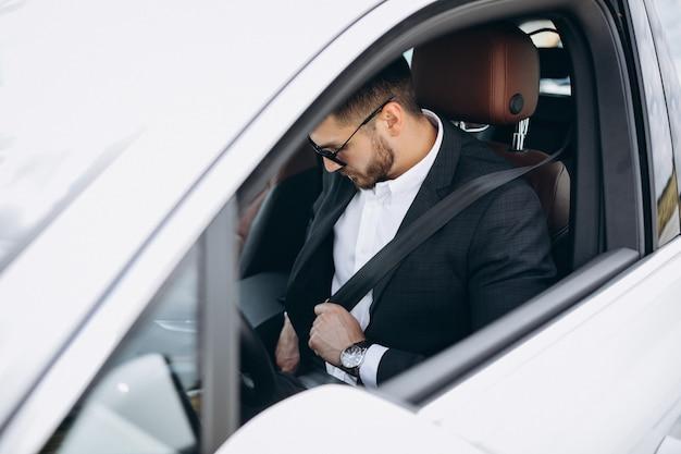 Knappe bedrijfsmens die in een auto reist Gratis Foto
