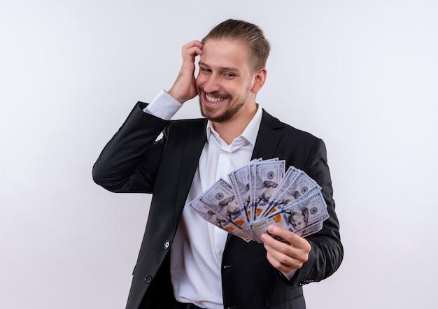 Knappe bedrijfsmens die kostuum draagt dat contant geld toont dat gelukkig en opgewekt geld bekijkt dat zich over witte achtergrond bevindt Gratis Foto