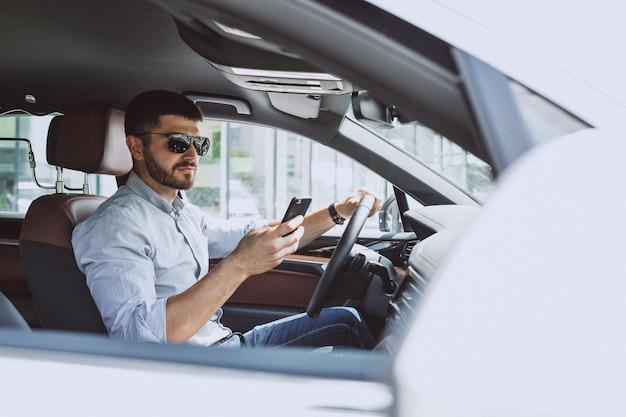 Knappe bedrijfsmens die telefoon in auto met behulp van Gratis Foto