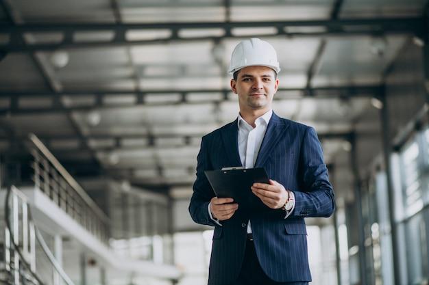 Knappe bedrijfsmenseningenieur in bouwvakker in een gebouw Gratis Foto