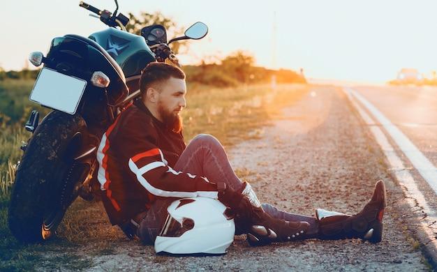 Knappe blanke bestuurder met mooie baard liggend op zijn motorfiets de linkerhand op de witte helm zetten tegen de zonsondergang Premium Foto