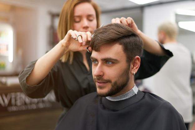 Knappe blauwogige man zit in de kapper. herenkapper kapper vrouw die zijn haar snijdt. vrouwelijke kapper. Premium Foto