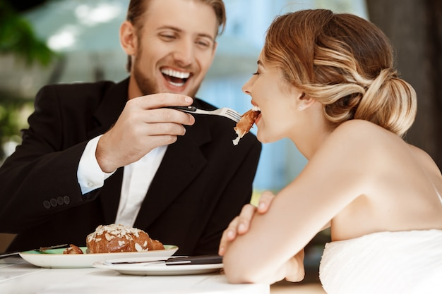 Knappe bruidegom die zijn bruid met croissant in koffie voeden. Gratis Foto