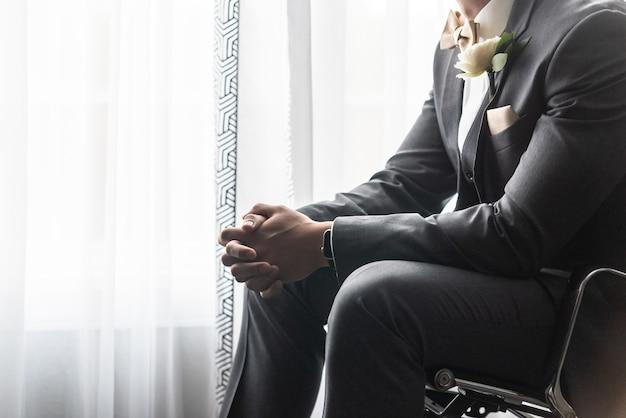 Knappe bruidegom in een zwart pak bidden voor de huwelijksceremonie Gratis Foto