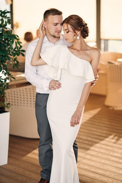 Knappe bruidegom knuffelen teder zijn mooie sensuele bruid in witte jurk op het terras Premium Foto
