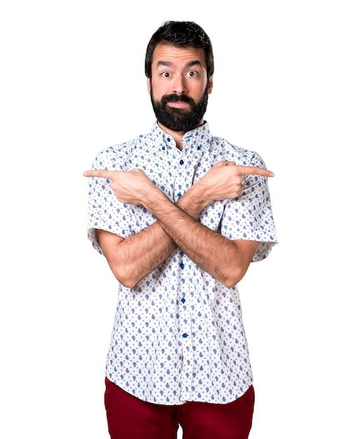 Knappe brunette man met baard naar de laterals wijzen die twijfels hebben Gratis Foto