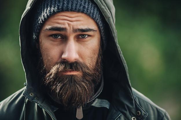 Knappe brutale bebaarde man met donkere baard en snor gekleed in winterkleren Premium Foto