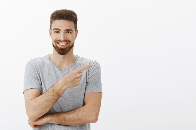 Knappe charmante onafhankelijke ondernemer met baard en cool kapsel in grijs t-shirt wijzend recht naar kopie ruimte en glimlachend verzekerd en opgetogen om mensen te vertellen over geweldig product Gratis Foto