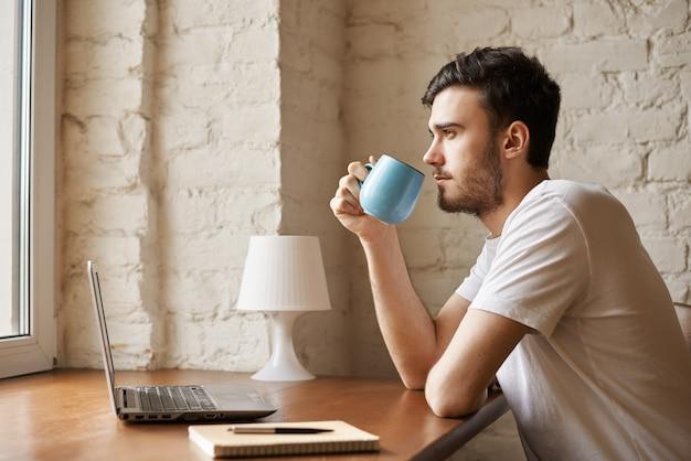 Knappe copywriter met stijlvolle baard kopje met koffie in de hand houden Gratis Foto